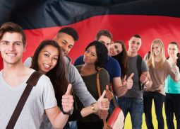 Group Of Multi Ethnic Students Standing In Front Of German Flag Showing Thumb Up
